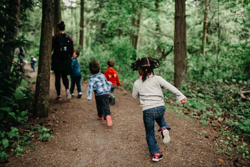 Young children run down a hiking path.
