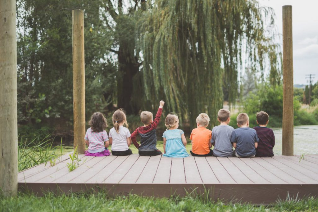 Group of young children sitting on a wooden dock, one with his fist in the air.