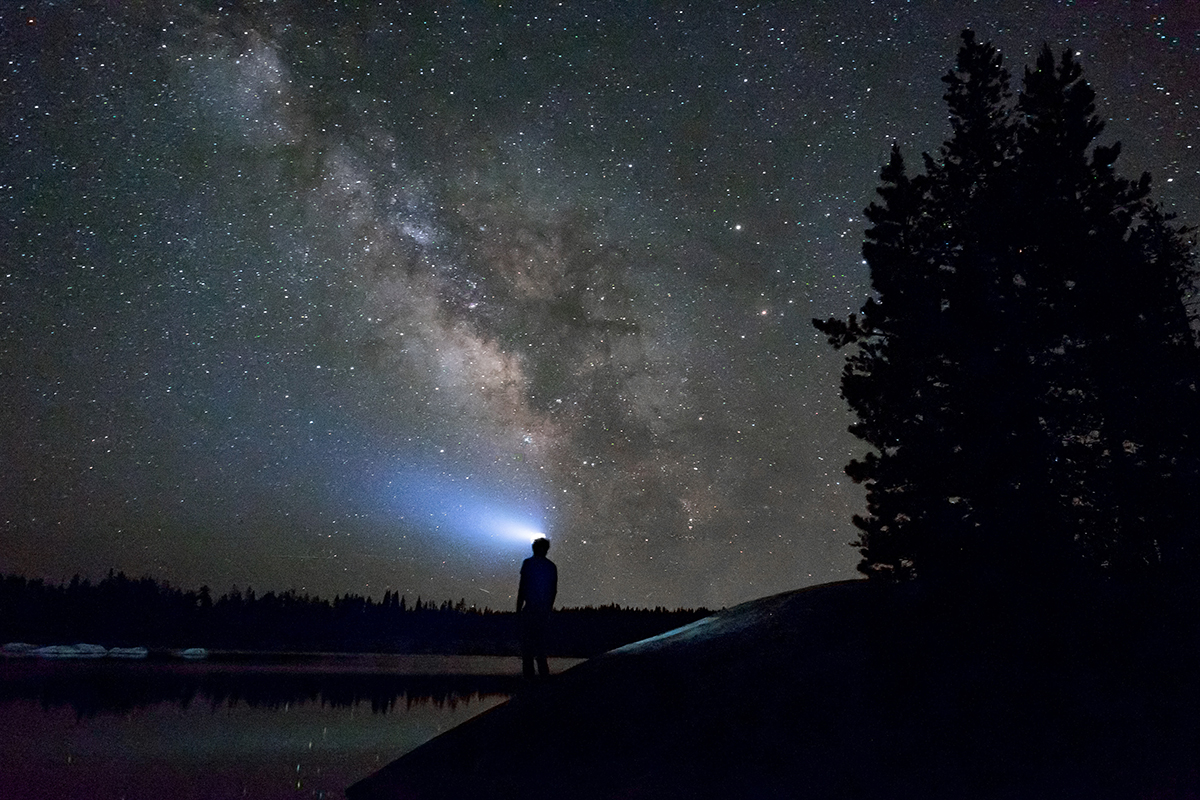 Man standing at water's edge in the night lit by the milkyway galaxy and his headlamp.