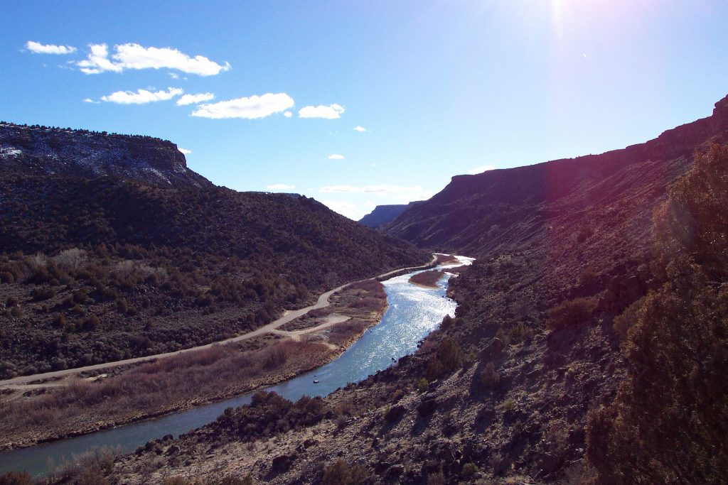 River and road winding through a rocky, arid valley.