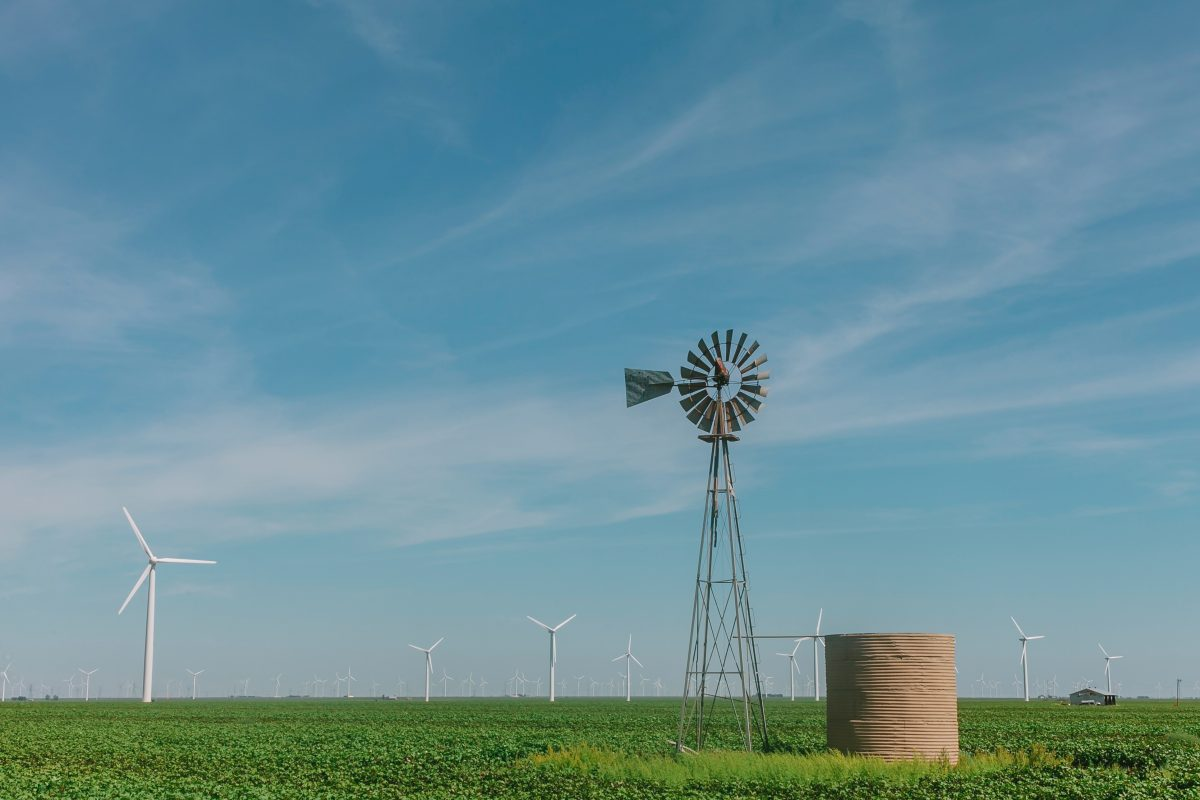 Old windmill in a green field, surrounded by modern windwills as far as the eye can see.
