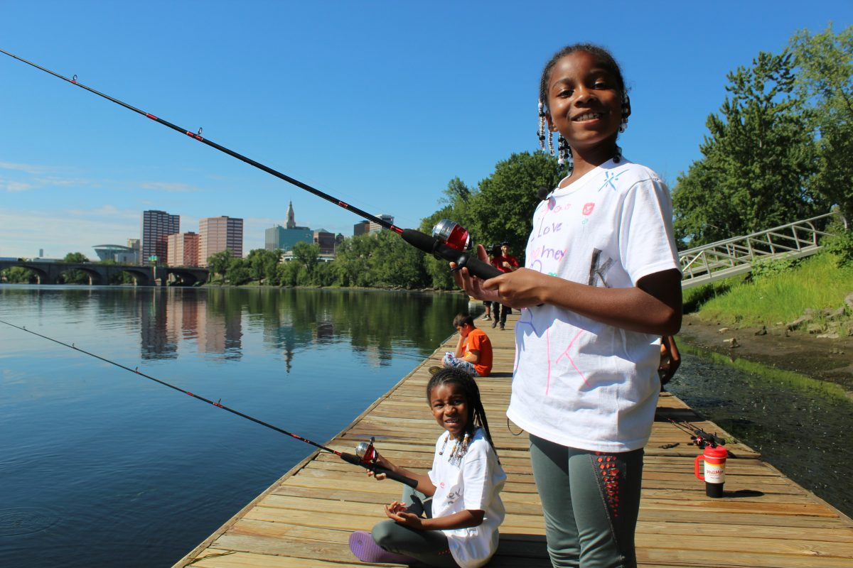 Children smiling while fishing from a wooden dock.