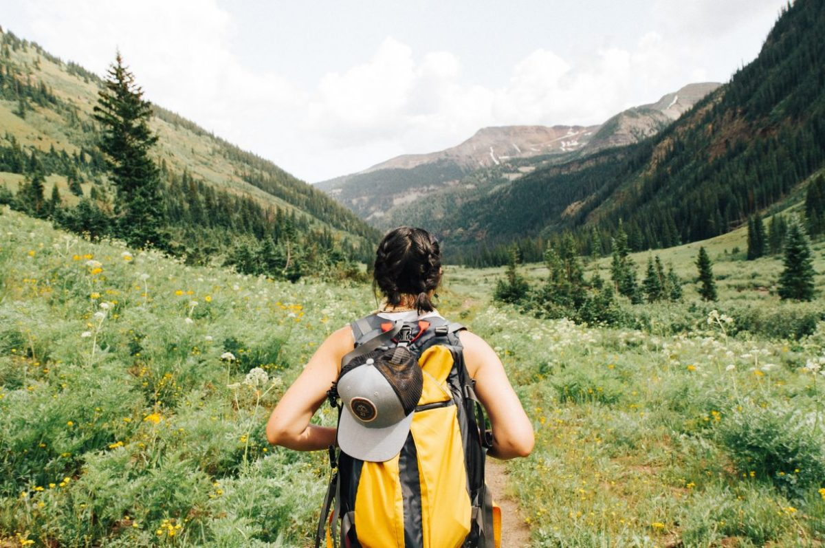 Woman backpacking through a green valley.