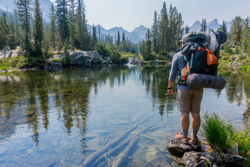 Hiker with a heavily loaded backpack stands on the bank of a pond.
