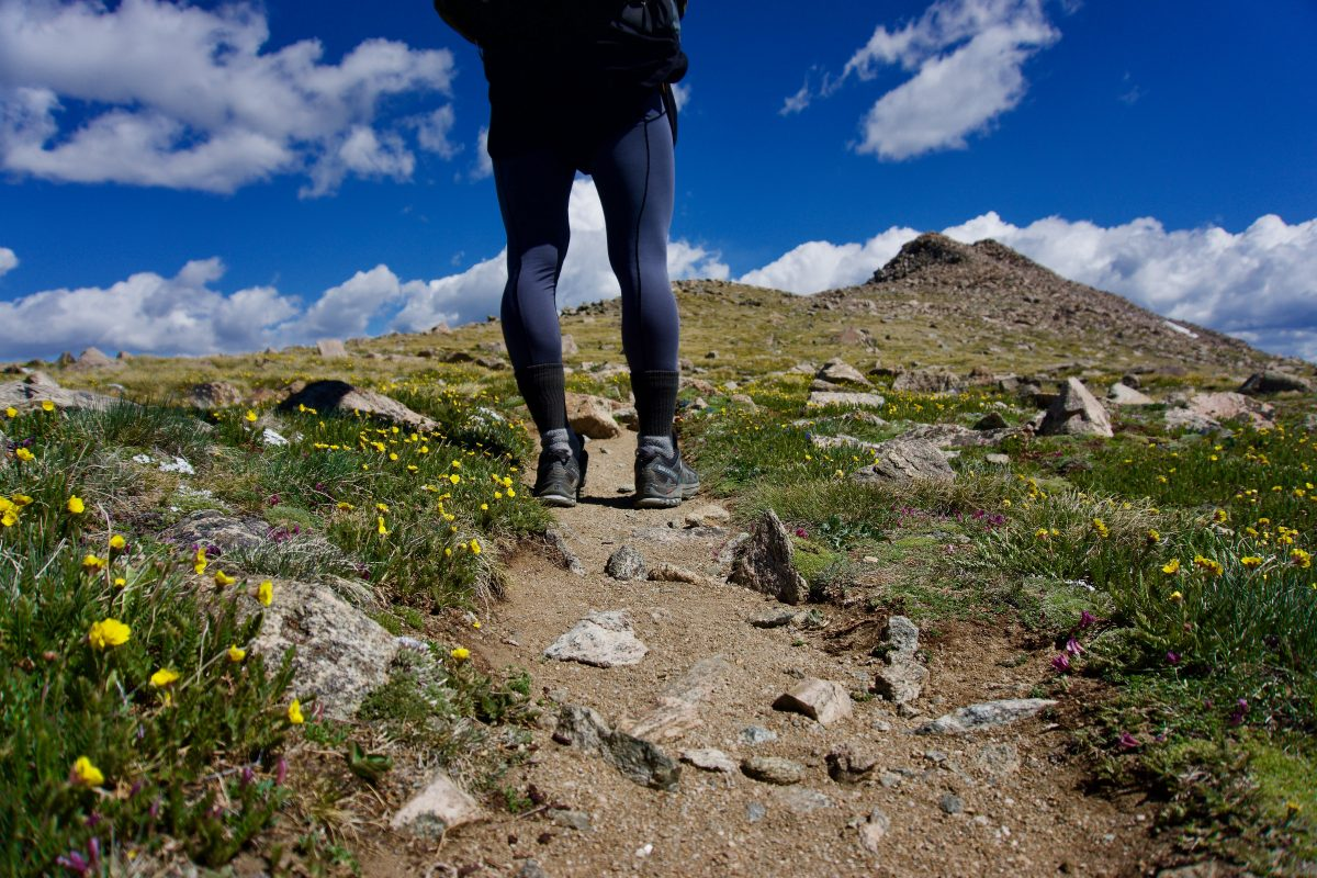 Hiker from the waist down standing on a rocky trail.